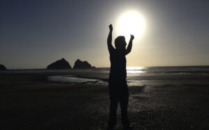 Silhouetted figure holding fists in the air